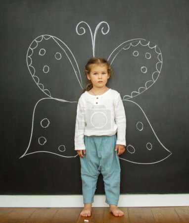 Photo for Little cute girl in a bright room, a minimum of objects in the room - Royalty Free Image