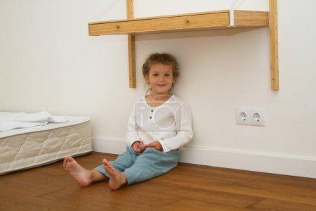 Photo pour Petite fille mignonne dans une pièce lumineuse, un minimum d'objets dans la chambre - image libre de droit