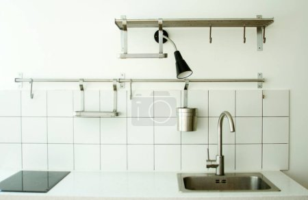 Photo for The interior of a bright kitchen, a minimum of items and furniture, a faucet and a sink in the foreground. - Royalty Free Image