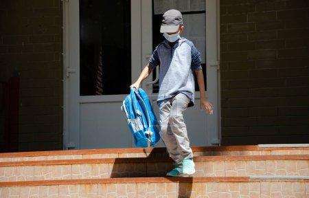 Photo pour Un mignon adolescent en masque médical sur son visage, une nouvelle normale, une école en quarantaine. - image libre de droit