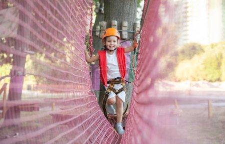 Foto de Una niña pequeña en un casco naranja y protección especial pasa por obstáculos en un parque de atracciones de cuerda, tiempo libre para niños, una zona de juegos para niños pequeños, diversión en el parque . - Imagen libre de derechos