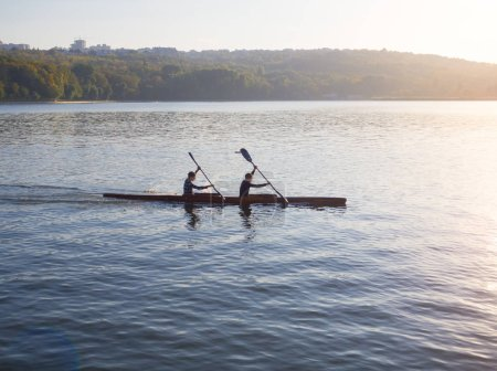 Two kayakers rowers on the lake. The concept of a healthy lifestyle.