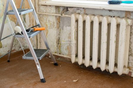 Photo pour Repair work in the apartment. Restoration indoors. Heating radiator with a rust and a metal stepladder against the background of old walls and wooden floor. Selective focus. - image libre de droit