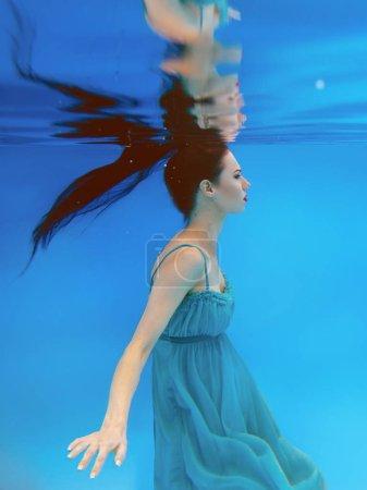 Photo pour Surréaliste, concept, portrait d'art de belle belle jeune femme brune avec maquillage sous l'eau dans la piscine sur fond bleu - image libre de droit