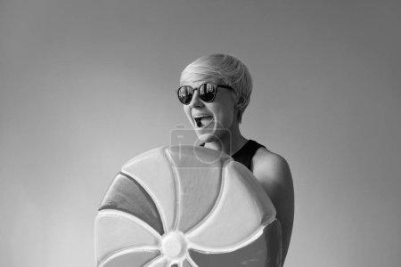 Photo pour Portrait monochrome d'une jeune femme blonde aux cheveux courts en lunettes de soleil noires, chemise noire mangeant une énorme sucette colorée sur fond de mur - image libre de droit