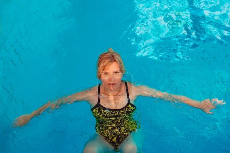 Funny emotional blonde woman in the swimming pool....
