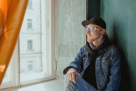 Photo for Portrait of modern redhead handsome stylish man in black hat and Jean jacket and glasses alone by the window. Fashion concept - Royalty Free Image