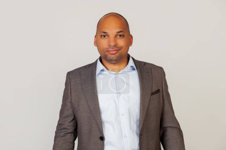 Junger afroamerikanischer Geschäftsmann, attraktiv grinsend, lächelnd, mit selbstbewusstem und kokettiertem Gesichtsausdruck in die Kamera blickend.