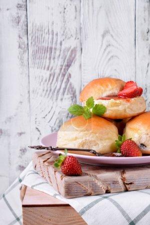 Photo pour Pains de levure avec la confiture de fraise et le beurre sur le fond en bois blanc. Sandwich de dessert - image libre de droit