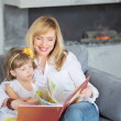 Mother and little daughter are playing, reading a ...