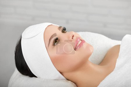 Smiling woman lying on white cosmetological coach ...