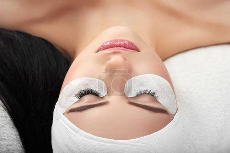 Girl lying in cosmetological cabinet during lashes...