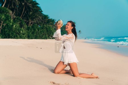 The model laughs standing on the beach on his knees, trying to pour water from the coconut into his mouth, laughing and having fun. A girl tries to drink a coconut pipe without a tube.
