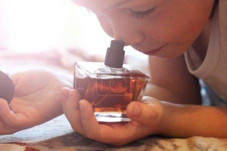 Photo pour L'enfant tient une bouteille de parfum si près - image libre de droit