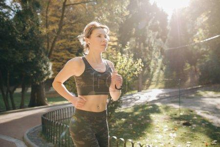 Foto de Retrato de atractivo corredor mujer morena en auriculares auriculares ciudad Parque airpods bluetooth. Mujer athletic fitness saludable trotar al aire libre - Imagen libre de derechos