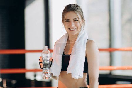 Photo for Thirsty fitness woman resting taking a break with water bottle drink inside after training - Royalty Free Image
