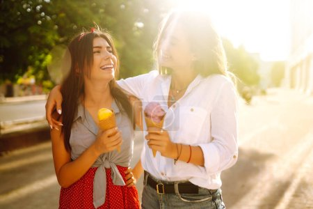 Two young female friends having fun and eating ice...
