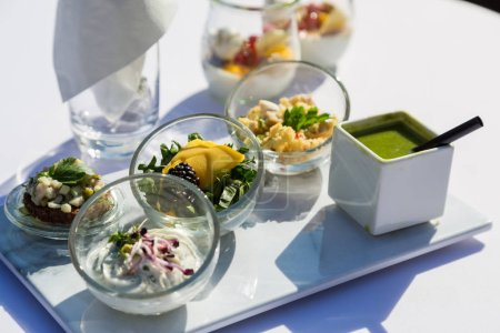 Vegetable, fish and meat snack in glass on table