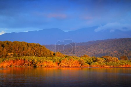 Rio Tarcoles, Carara National Park, Costa Rica. Sunset in beautiful tropical forest landscape. Meanders of river Tarcoles. Hills with orange evening sky. Holiday in Costa Rica. Mountains and clouds.