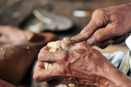 Close-up of hand of an elderly Thai man produces hand made wood carving according to ancient tradition. Concept of: world culture, weaving and tailoring, tradition.
