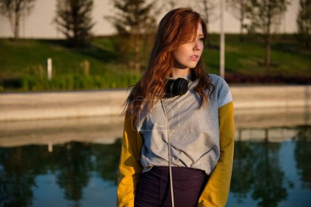 Photo for Red-haired girl in a sweatshirt with headphones on her neck stands on the street against the backdrop of a pond and looks away, in the sunset light - Royalty Free Image