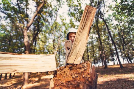Photo for A boy chopped wood with an ax in a forest on a stump, wide angle HDR photo. - Royalty Free Image