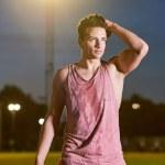 Portrait of a young muscular sweat sportsman posin...