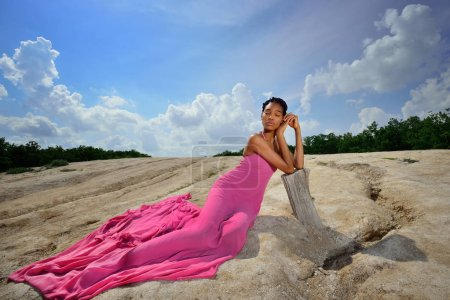 A lovely African American girl, with dreadlocks, lies in a pink dress on a high hill against the sky, leaning on a dry tree. She put her hands under her head, closed her eyes and dreamed. Bottom view.