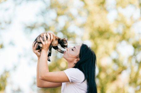 Photo pour Joyeuse jeune femme avec chat mignon dans le parc - image libre de droit