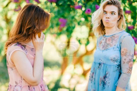 Photo for Young twin sisters in different dresses in blooming summer botanical garden - Royalty Free Image