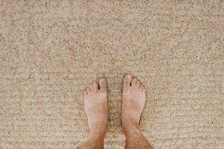Photo pour Vue partielle de l'homme aux pieds nus sur la plage de sable fin - image libre de droit