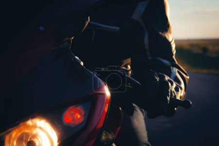 Photo for The young guy is sitting in a red motorcycle - Royalty Free Image