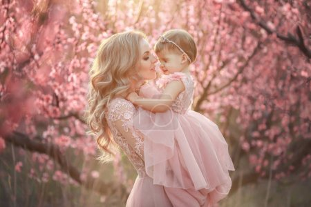 Photo for Portrait of young beautiful mother with her little girl. Close up still of loving family. Attractive woman holding her child in pink flowers and smiling. - Royalty Free Image