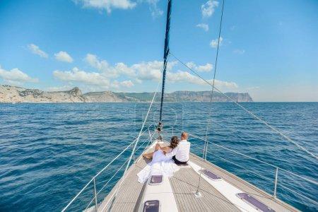 Photo pour Un couple juste marié sur le yacht. Mariée et marié heureux le jour de leur mariage. - image libre de droit