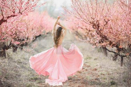 Photo pour Une jeune princesse se promène dans un jardin fleuri. Fille dans une robe rose luxueuse avec un train. Tonification à la mode - image libre de droit