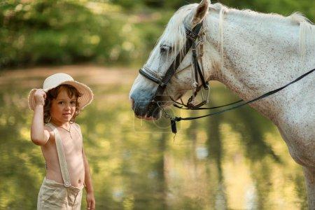 Photo pour Petit garçon aux cheveux bouclés habillé comme un hobbit jouant avec le cheval dans la forêt d'été . - image libre de droit