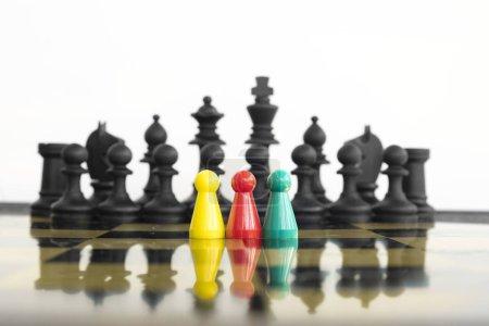 Groupe de pions colorés debout devant toute une armée d'échecs noirs face au risque d'une confrontation .