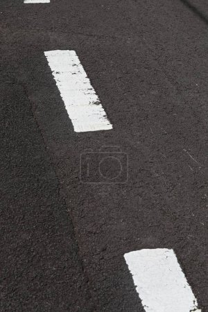 Photo for Close up straight and smooth asphalt road of black color with one continuous marking. Blue sky background - Royalty Free Image