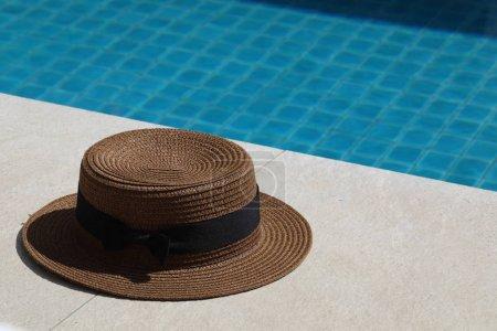 Photo pour Près de la piscine est un chapeau de paille avec un arc noir - image libre de droit