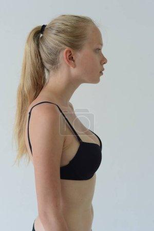 Photo pour Belle mannequin tests fille en lingerie noire avec tatouage posant dans Studio sur fond gris - image libre de droit