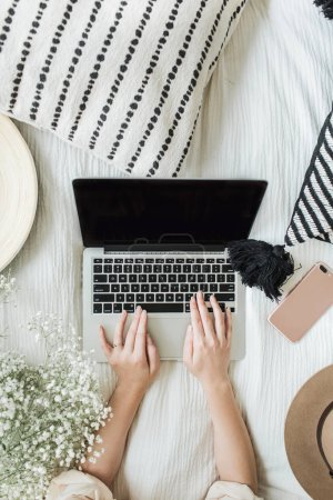 Photo for Young woman working on laptop in bed. Lifestyle composition with view from above decorated with white flowers bouquet, pillow, hat, cell phone and wooden plate. Freelancer or fashion blogger home workspace concept. - Royalty Free Image