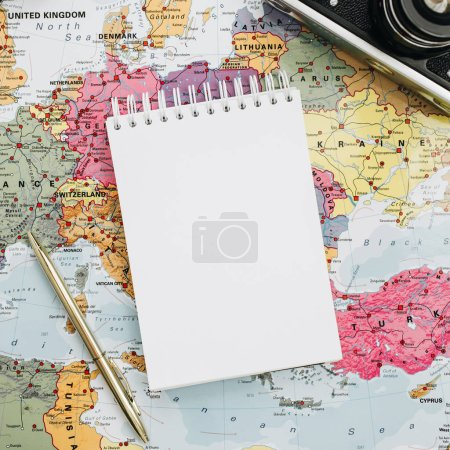 Travel notes mock up with paper blank. Europe map, camera, sunglasses and notebook. Flat lay, top view.