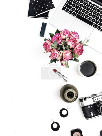Woman fashion home office desk. Workspace with laptop, rose flowers bouquet, retro camera, accessories and cosmetics on white background. Flat lay, top view stylish female mockup.