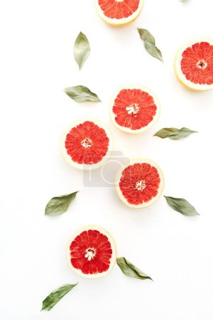 Photo for Red sliced grapefruits and green leaves on white background. Flat lay, top view food concept. - Royalty Free Image
