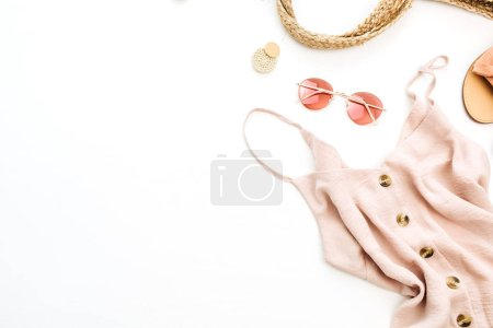 Summer pink woman's stylish clothes and accessories on white background. Flat lay, top view. Summer fashion concept.