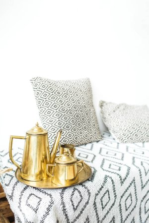 Modern minimal home interior design. Pillows, golden teapot, tray, Scandinavian blanket.