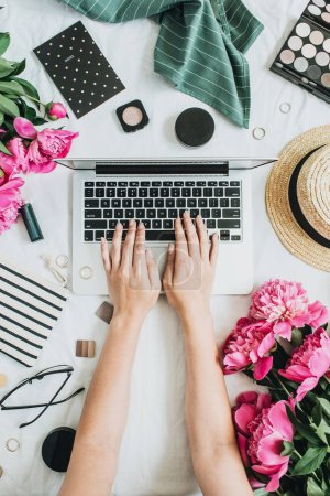 Woman working on laptop. Flat lay, top view female office desk workspace with pink peony flowers bouquet, accessories and cosmetics. Fashion, beauty or lifestyle blog concept.