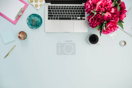 Workspace with laptop and pink peony flowers bouquet on blue background. Flat lay, top view home office desk.