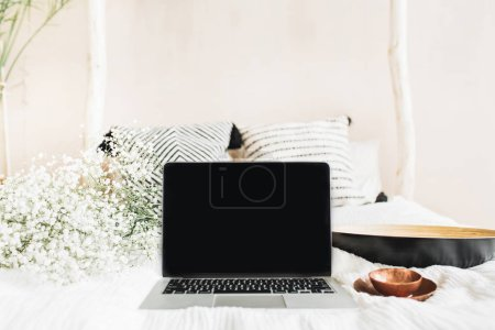 Freelancer workspace with laptop with blank screen, vintage saucer, white flowers. Front view mock up template. Blog hero header concept.