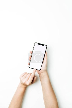 Photo pour Femme toucher à la main vierge écran de téléphone intelligent. Pose plate, modèle de maquette de vue supérieure . - image libre de droit